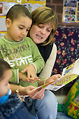 A nursery worker reads a book to a child at Emmanuel Playgroup in the Lydford Estate Tenants' Hall, Paddington, London