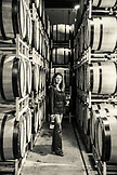 USA, Oregon, Willamette Valley, Dyane Savino stands amidst barrels of wine in the barrel room at Domaine Drouhin, Dundee