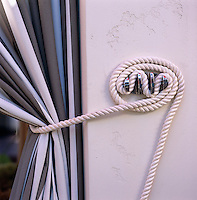 Detail of the rope tie-back used to restrain the striped curtains around the pool dining area