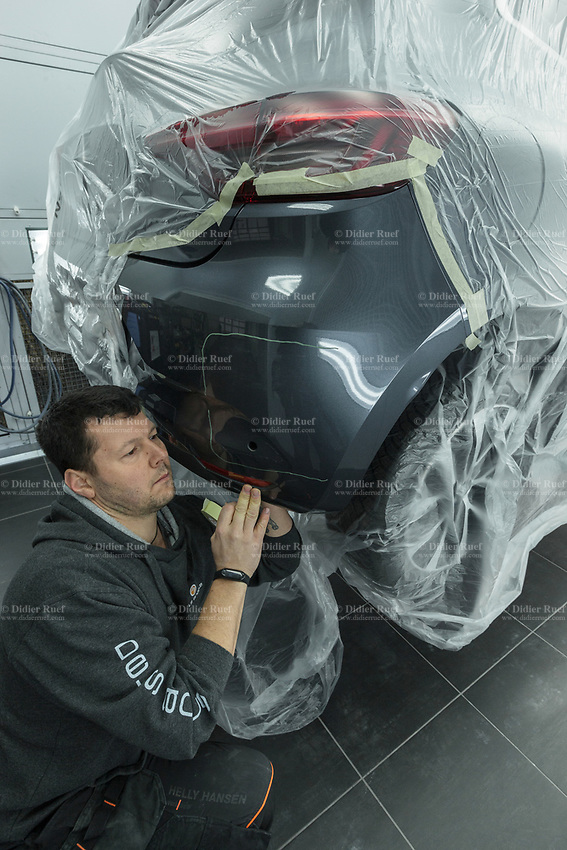 "Switzerland. Canton Geneva. Plan-les-Ouates. Renault Retail Group, RRG Suisse. ""Spot-repair"" by Dells Angels. Renault Clio car inside a paint booth in auto body repair garage. A worker covers the car with plastic sheet. 4.03.2020 © 2020 Didier Ruef"