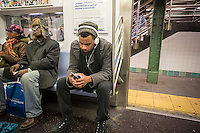 A music listener wears his over the ear headphones, while listening to music on his Samsung smartphone in a subway car in New York on Wednesday, February 11, 2015 (© Richard B. Levine)