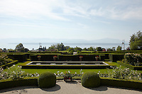 A gravel parterre opens onto a manicured lawn with a rectangular pond framed by a low box hedge