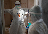 Health care worker Selina B. Davis is sprayed down with a strong mix of chlorine and water as she doffs her PPE at the ELWA II ETU (Ebola treatment unit) in Monrovia, Liberia on Sunday, March 1, 2015. Miller wears her portrait, created as part of Occidental College professor Mary Beth Heffernan's PPE Portrait Project.<br /> (Photo by Marc Campos, Occidental College Photographer) Mary Beth Heffernan, professor of art and art history at Occidental College, works in Monrovia the capital of Liberia, Africa in 2015. Professor Heffernan was there to work on her PPE (personal protective equipment) Portrait Project, which helps health care workers and patients fighting the Ebola virus disease in West Africa.<br />