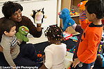 Preschool 2-3 year olds female teacher and children using puppets to play and talk