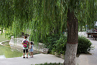 People walk along a pond in Changle Park in Xian, Shaanxi Province, China.