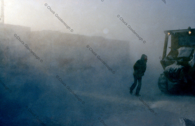 Stock Photo taken out on the ice of the Beaufort Sea, north of the coast of Alaska. A worker, catskinner caterpillar driver is heading to his rig during a blowing snow between trailers used for housing oil exploration workers and scientists.