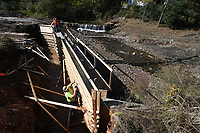 NWA Democrat-Gazette/J.T.WAMPLER Workers from the transportation department remove the wooden form Thursday Oct. 31, 2019 after a concrete footing was poured for a bridge over the creek for the Niokaska Creek Trail near Crossover Rd. In Fayetteville. The trail will connect the Razorback Greenway to Gulley Park by providing an extension from Mud Creek Trail at Old Missouri Road and is scheduled to be done late 2019.