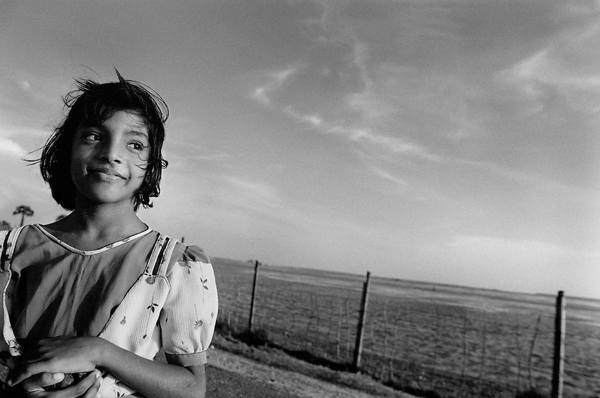 A Tamil girl walks home along a lagoon road on the outskirts of Jaffna, Sri Lanka, Thursday, Apr. 22, 2004.