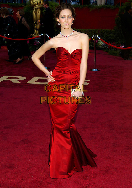 EMMY ROSSUM.Red Carpet Arrivals, 77th Annual Academy Awards held at the Kodak Theatre, Hollywood, California, USA, .27th February 2005.  .oscars full length red starpless dress hand on hip clutch bag jewellery.Ref: ADM.www.capitalpictures.com.sales@capitalpictures.com.©JWong/AdMedia/Capital Pictures