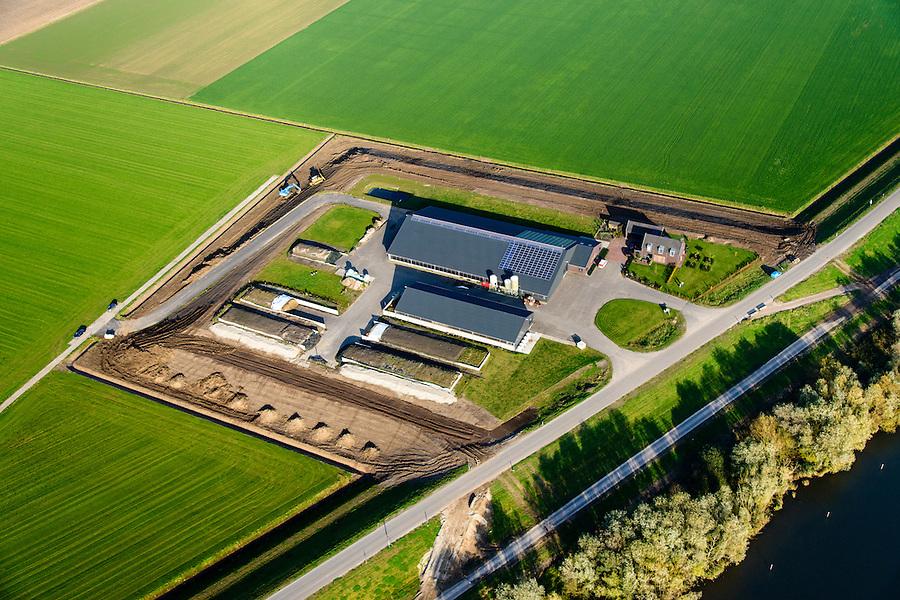Nederland, Brabant, Gemeente Waspik, 28-10-2014; Overdiepsche polder: in het kader van het programma 'Ruimte voor de Rivier' (bescherming tegen hoogwater door rivierverruiming), is de dijk langs de Bergsche Maas (buiten beeld) verlaagd. Bij hoogwater kan de Overdiepse polder overstromen. De boerderijen in de polder zijn gesloopt en verplaatst naar de dijk van het Oude Maasje. De nieuwe boerderijen met bijgebouwen staan op terpen.<br /> Depoldering of Overdiep Polder, farms are relocated and built on mounds. This makes it possible for the river to overflow the polder in case of heigh waters.<br /> luchtfoto (toeslag op standard tarieven);<br /> aerial photo (additional fee required);<br /> copyright foto/photo Siebe Swart
