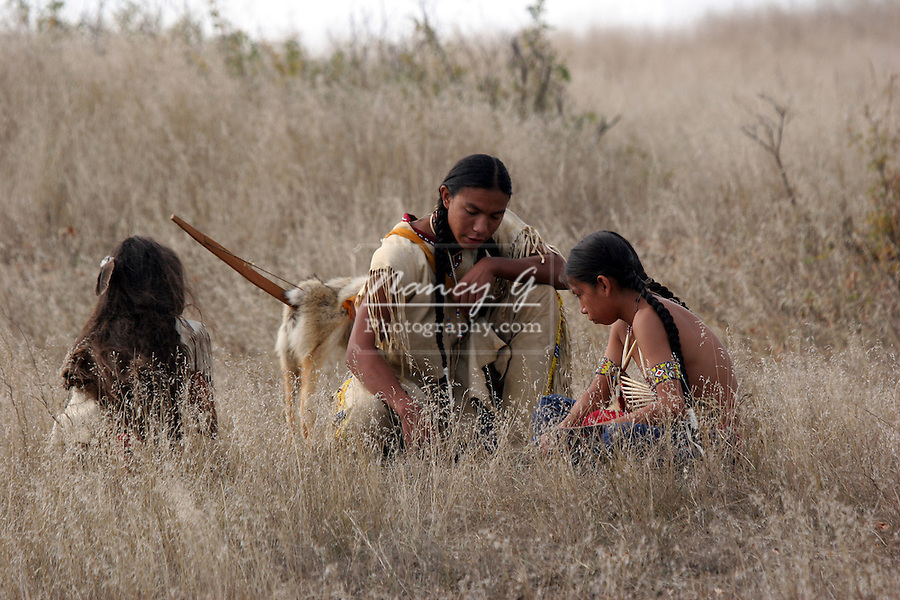 Three Native American Indian Children using the ground to show a map of the location of the game or food