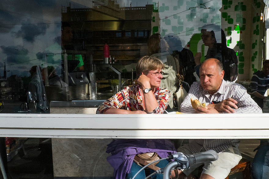 Nederland, Amsterdam, 1 juli 2013<br /> Mensen eten een broodje voor het raam in een broodjeszaak<br /> Foto(c): Michiel Wijnbergh