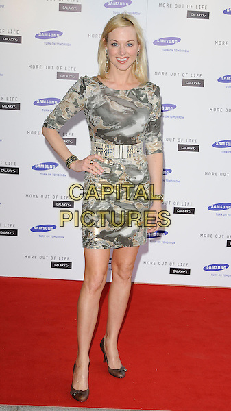 SARAH MANNERS .attends the launch of the Samsung Galaxy S Smartphone held at Altitude Bar, London, England, UK, .June 15th, 2010. .full length hand on hip grey gray cream print dress gold waist belt smiling silver brown shoes .CAP/CAN.©Can Nguyen/Capital Pictures.