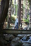 USA, California, Big Sur, Esalen, a woman walks across a bridge over Hot Springs Creek at the Esalen Institute