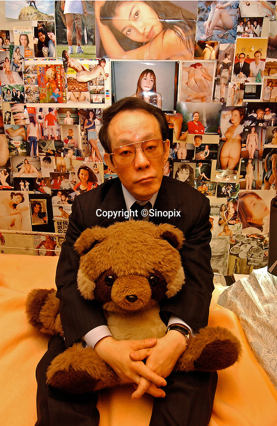 "Issei Sagawa, the notorious Japanese cannibal, poses with his ""baby"" (a stuffed panda) next to erotic photo collages in his bedroom. The collages contain images of Western and Asian  women he has dated and photographed. Sagawa killed and ate  Dutch student Renee Hartevelt while studying in Paris in 1981. He was released in Japan due to political connections after being jailed then placed in a mental institution in Paris. <br /> 14-DEC-05"