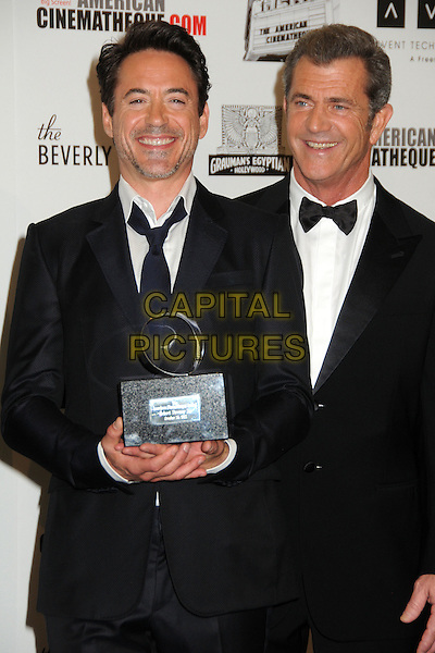 Robert Downey Jr. and Mel Gibson.25th Annual American Cinematheque Award Ceremony Honoring Robert Downey Jr. held at the Beverly Hilton Hotel, Beverly Hills, California, USA, .14th October 2011..half length award trophy black suit tie bow tuxedo white shirt smiling navy blue .CAP/ADM/BP.©Byron Purvis/AdMedia/Capital Pictures.