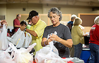 NWA Democrat-Gazette/JASON IVESTER <br /> Virgie (cq) Brown of Rogers helps bag food items on Thursday, Aug. 27, 2015, inside the Samaritan Community Center in Rogers for the Snackpacks for Kids program. The group from First United Methodist Church of Rogers volunteers monthly at the center. The program supplies food for over 7700 students in the region from headstart through high school.