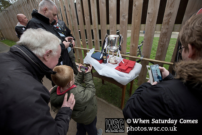 Cefn Druids AFC 1 Buckley Town 0, 12/04/2014. The Rock, Cymru Alliance league. Fans taking photographs of the league trophy at The Rock, Rhosymedre, home to Cefn Druids AFC, during the club's final home game of the season against Buckley Town (in yellow) in the Cymru Alliance league. Druids, reputedly the oldest football club in Wales, won the Alliance league the previous week and were awarded the trophy after the Buckley Town match, which they won by 1 goal to nil, watched by a crowd of 246. The Cymru Alliance was the second tier of Welsh football based in north and mid Wales, promotion from which led directly into the Welsh Premier League. Photo by Colin McPherson.