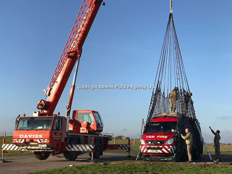 Pictured: A crane helps unload a fire engine to Caldey Island off the Pembrokeshire coast, Wales, UK. Tuesday 24 January 2017<br /> Re: A Fire and Rescue Appliance has been delivered to Caldey Island via Chinook Helicopter. <br /> Mid and West Wales Fire and Rescue Service and the RAF have flown a Rural Response Pump to Caldey Island.<br /> The island, off Tenby in Pembrokeshire is inhabited by Cistercian Monks