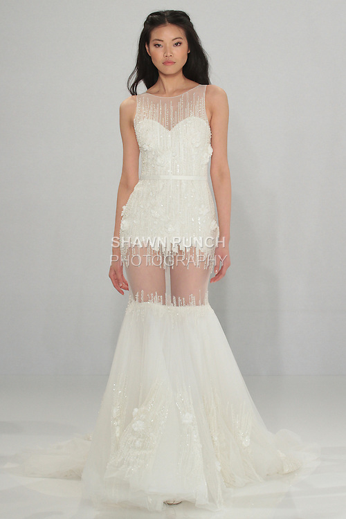 """Model walks runway in Olwen - an off white mermaid-cut tulle dress with vertical lines of crystal embroidery and a belt on the waistline, from the Tony Ward Fall 2016 """"A Mid-Summer Night's Dream"""" bridal collection on April 18, 2016 at Kleinfeld Bridal during New York Bridal Fashion Week Spring Summer 2016."""