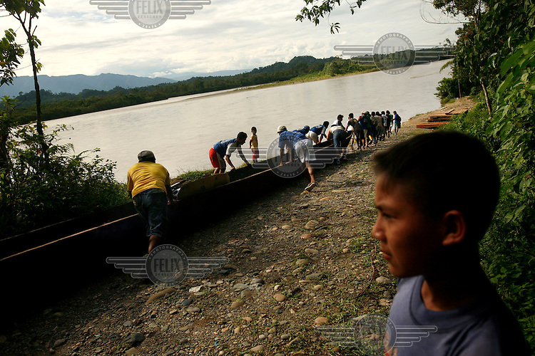 A boy watches as men test out a new canoe that will be used by the people in the Quichua community of San Pedro Sumino.