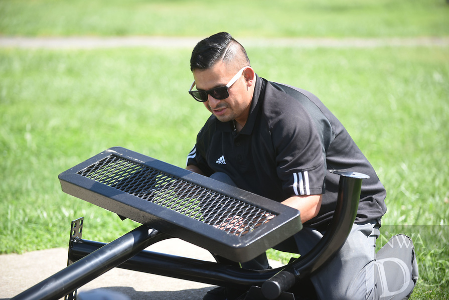 NWA Democrat-Gazette/FLIP PUTTHOFF <br />OUTDOOR SEATING<br />German Martinez (cq) with Bentonville Parks and Recreation assembles a picnic table Tuesday April 18 2017 at Memorial Park. Martinez worked on the tables near the Melvin Ford Aquatic Center.