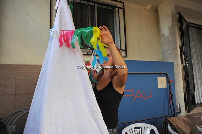 """A woman prepares a fake teepee for her """"penya,"""" or group of friends calling themselves """"Els Kutos,"""" or """"the pigs"""" in Catalan, as part of their Native American attire for Costume Night celebrations during the municipal fiestas in the town of Costur, Spain on August 17, 2009."""