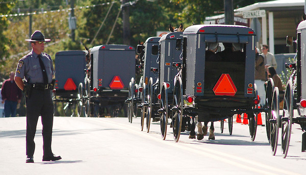 A Pennsylvania Stae Policeman watches as the funeral procession for one of the Nickel Mines Amish schoolhouse shooting victims roll through the village of Georgetown, Pennsylvania October 5, 2006. Amish mourners in their horse and buggies follow to the cemetery for the burial service. REUTERS/Bradley C Bower (UNITED STATES)
