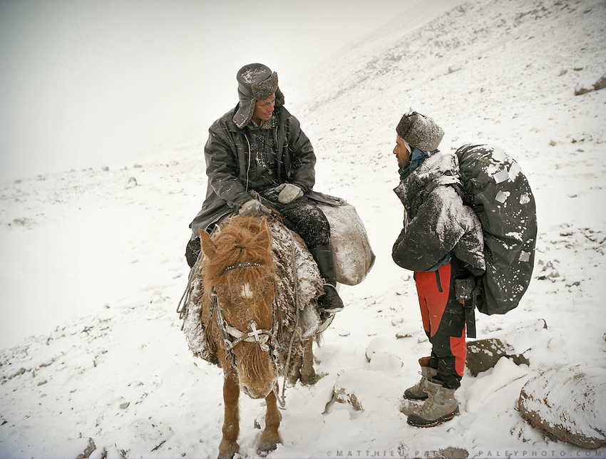Malang (R), meet a horse rider. Arriving campment of Ortobil (Sufi), all the way at the end of the Little Pamir, near the Tajik/China border. .Winter expedition through the Wakhan Corridor and into the Afghan Pamir mountains, to document the life of the Afghan Kyrgyz tribe. January/February 2008. Afghanistan