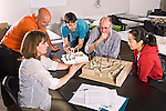 Five adult men and women work on design for landscape architecture with models in classroom in adult education