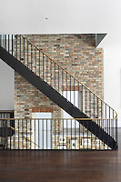 The central stairwell of the London townhouse, with iron balustrades and a brass handrail