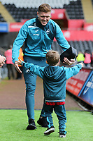 Alfie Mawson of Swansea City is embraced by a young boy as he arrives prior to the game during the Premier League match between Swansea City and Crystal Palace at The Liberty Stadium, Swansea, Wales, UK. Saturday 23 December 2017