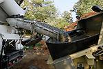 Concrete truck empties a load into the hopper of a concrete pump machine; action, slight blur.