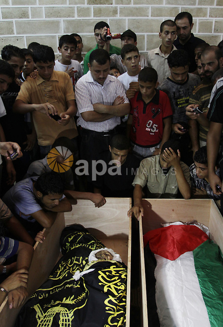 Palestinians mourn over the bodies of Moataz Qreqa, a commander of Islamic Jihad's Al-Quds Brigade, his five-year-old son Islam and his brother Munzer during their funeral in Gaza City on August 20, 2011 after all three were killed when Israeli planes launched air strikes in Gaza in retaliation for suspected Islamist militants killing eight Israelis near the Egyptian border. Photo by Naaman Omar
