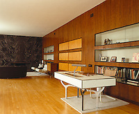 Built-in wall units covered with Indian laurel run the length of the living room with a vinyl-covered desk on aluminium legs designed by Gwynne