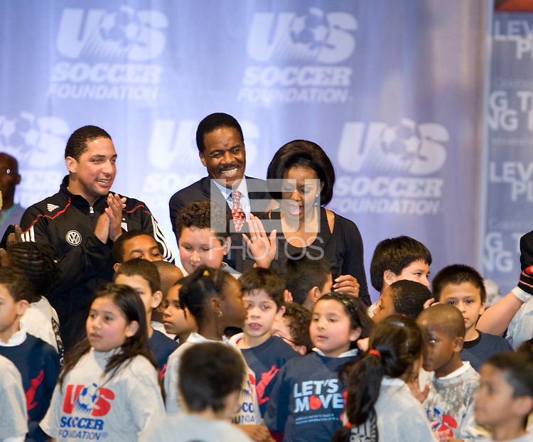 First Lady Michelle Obama high-fives a group of local students after a US Soccer Foundation clinic held at City Center in Washington, DC.