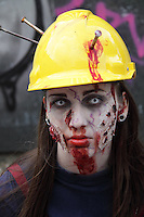 Female participant in the prague Zombi walk in may 2014. Wearing a yellow builders helmet with 3 nails hammered into it, having blood painted n her face. Headshot.