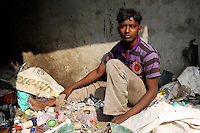 A man sits amongst recently collected trash in a small community in Kolkata.<br />