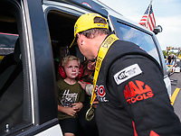 Oct 7, 2018; Ennis, TX, USA; NHRA top fuel winner Steve Torrence (right) consoles Cameron McMillen, son of losing finalist Terry McMillen as he cries after winning the Fall Nationals at the Texas Motorplex. Mandatory Credit: Mark J. Rebilas-USA TODAY Sports