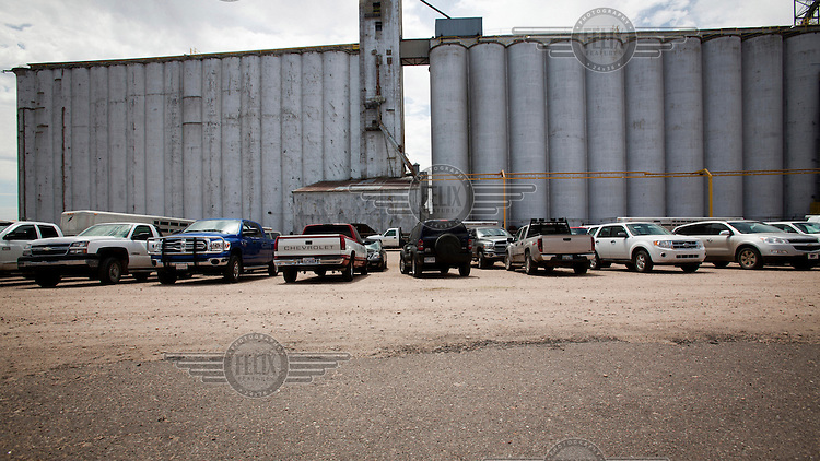 Cattle rancher's vehicles parked by a grain storage elevator while their owners attend a nearby cattle auction, near Dodge CIty, Kansas.