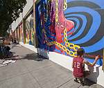 Nathaniel Benjamin signs his work during the Mural Marathon on Sunday July 1, 2018 in downtown Reno.
