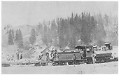 Engine and flatcar carrying stones.  A number of men are on and around the train.  Most likely a mining camp scene.<br /> D&amp;RG