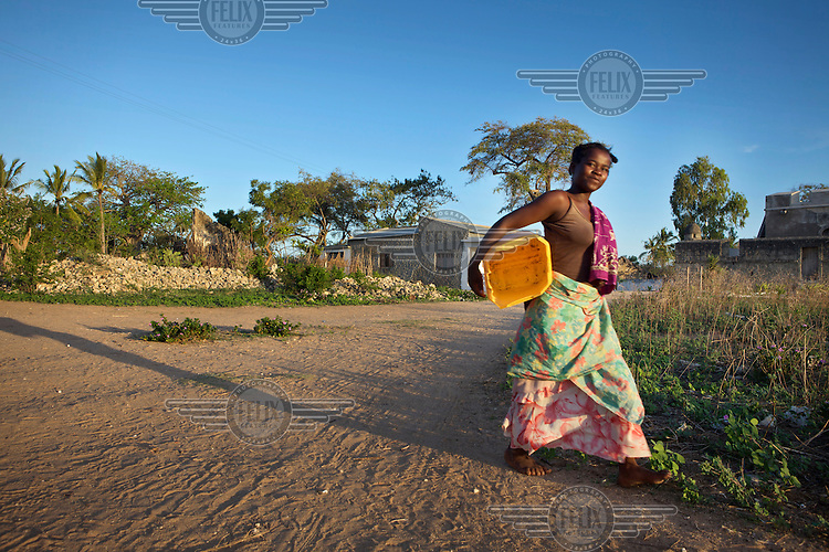 A woman carries a bucket on Ibo Island.