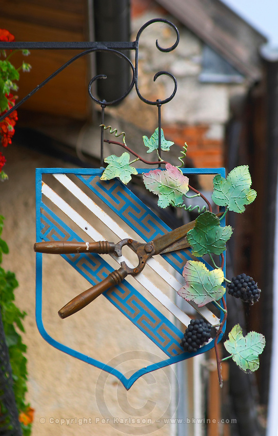 A wrought iron painted sign that illustrates the theme of champagne and wine production: a secateur on a coat of arms and a vine with bunches of grapes, the village of Hautvillers in Vallee de la Marne, Champagne, Marne, Ardennes, France