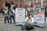 Nederland - Amsterdam - januari 2020.    De FNV roept op Fat Cat Day de veertien meest invloedrijke CEO's van ons land op om zich uit te spreken voor een hoger minimumloon. De meeste van deze CEO's hebben op 5 januari al het bedrag verdiend waar een minimumloner een heel jaar voor moet werken. De nummer 1, Ben van Beurden van Shell, heeft dat jaarloon op 1 januari om 14.26 uur al verdiend. Veertien mensen in kattenpakken lopen vandaag vanaf het Centraal Station in Amsterdam naar het Beursplein. Met biologisch afbreekbare olijfolie vermengd met as wordt milieuvervuiling door Shell nagebootst.      Foto mag niet in schadelijke context voor de actievoerders gepubliceerd worden.    Foto Berlinda van Dam / Hollandse Hoogte