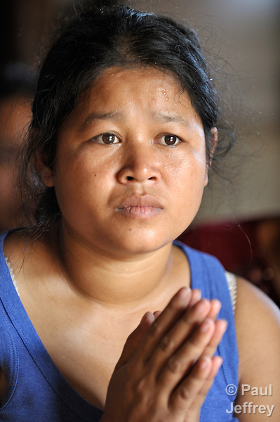 Member of a self-help group in the Phnom Penh neighborhood of Sen Rikreay, Chaum Siem, 29, listens raptly as a Buddhist monk addresses the group. Many people in this community are infected or affected by HIV and AIDS, and Buddhist monks and other religious meet with them regularly to mediate and discuss their challenges.