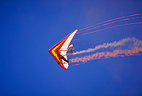Hang glider pilot Dan Buchanan waves hand in low level pass; streamers trail from wing; smoke trails from wheels. Dan Buchanan. Watsonville California.
