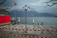 "Switzerland. Canton Ticino. Lugano. A police line forbids the access to the lake because of coronavirus (also called Covid-19). Due to the spread of the coronavirus , the Federal Council has categorised the situation in the country as ""extraordinary"". It has issued a recommendation to all citizens to stay at home, especially the sick and the elderly. The Federal Council (German: Bundesrat, French: Conseil fédéral, Italian: Consiglio federale, Romansh: Cussegl federal) is the seven-member executive council that constitutes the federal government of the Swiss Confederation. From March 16 the government ramped up its response to the widening pandemic, ordering the closure of bars, restaurants, sports facilities and cultural spaces. Only businesses providing essential goods to the population – such as grocery stores, bakeries and pharmacies – are to remain open. Lake Lugano (also called Ceresio) is a glacial lake which is situated on the border between southern Switzerland and Northern Italy. The flag of Switzerland displays a white cross in the centre of a square red field. The white cross is known as the Swiss cross. 22.03.2020 © 2020 Didier Ruef"