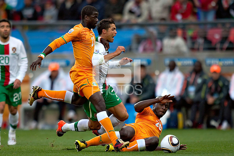 Christiano Ronaldo of Portugal is tackled by Emmanuel Eboue (left) and Guy Demel (right) of Ivory Coast..