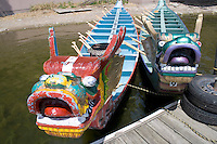 Pair of ferocious Asian dragon race boats moored at dock. Dragon Festival Lake Phalen Park St Paul Minnesota USA